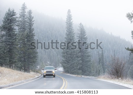 Winter cold weather vehicle icy driving on mountain road with pine trees in snow - stock photo