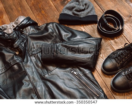 Winter collection of men's clothing in casual style on the wooden background. new men's leather winter jacket, hat, belt and shoes. Horizontal Photo - stock photo