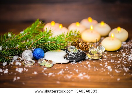 winter concept of Chinese New Year with Yin-Yang symbol, eight candles, cones, blue, silver balls, fir tree, ice and snow, closeup - stock photo