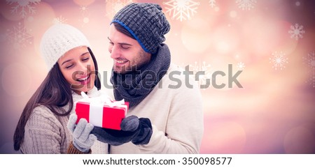Winter couple holding gift against glowing christmas background - stock photo