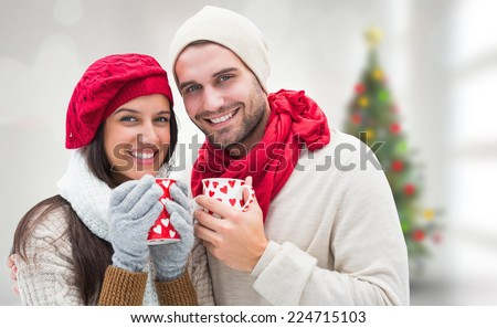 Winter couple holding mugs against blurry christmas tree in room - stock photo