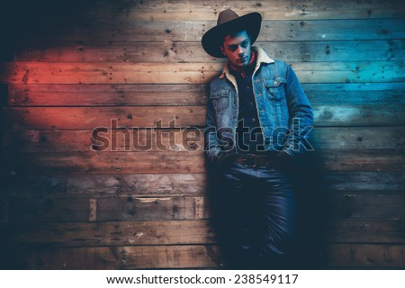 Winter cowboy jeans fashion man. Wearing brown hat, jeans jacket and trousers. Leaning against old wooden wall. - stock photo