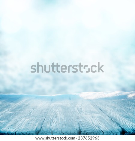 Winter day and wooden empty table in snow - stock photo