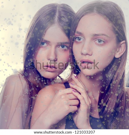 winter december two girls under snow wind snowflakes background - stock photo