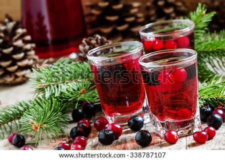 Winter drink with cranberry, cowberry and black chokeberry on the old wooden background with fir branches, selective focus - stock photo
