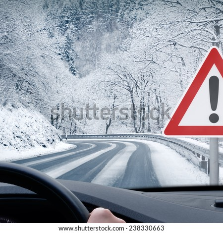 Winter Driving - Caution Snow - Curvy snowy country road - stock photo
