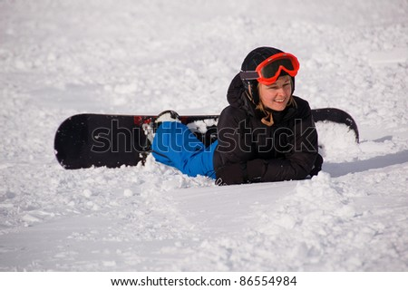 Winter entertainment/Smiling female snowboarder laying on snow - stock photo