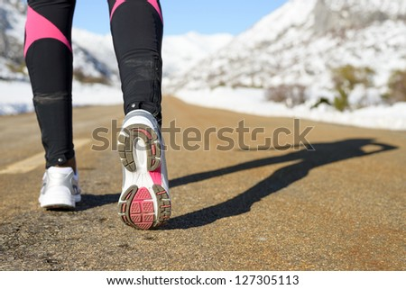 Winter exercising and run concept on mountain road. Female runner shadow and sport footwear.  Copy space - stock photo