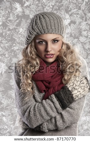 winter fashion shot of a beautiful girl with long curled blonde hair wearing a grey woolen cap, a grey sweater and warm gloves - stock photo