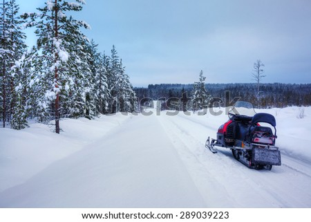 Winter Finnish snowy lanscape with road and snowmobile - stock photo