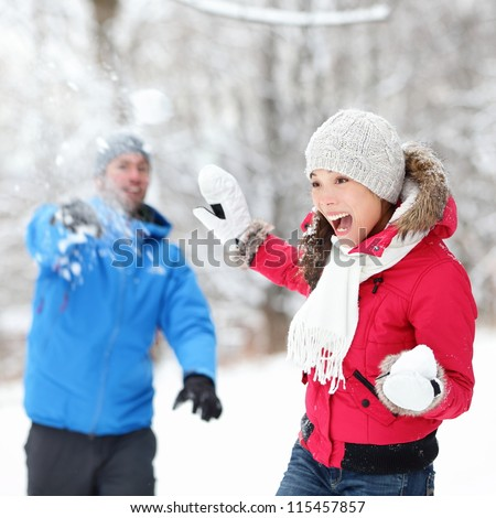 Winter fun - couple in snowball fight having fun together in forest snow landscape. Happy young interracial couple playing together in the snow. - stock photo