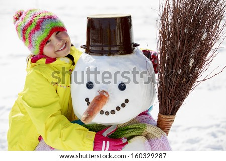 Winter fun, happy kid playing with snowman - stock photo