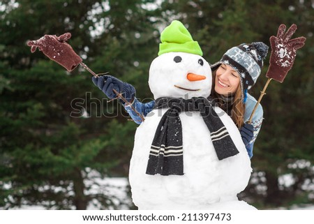 Winter fun, winter leisure and winter vacation - young happy woman have fun in wintertime making snowman - stock photo