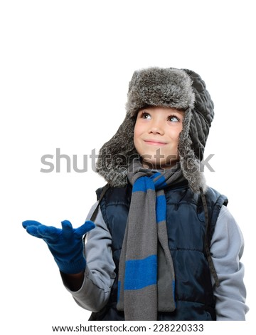 Winter fur hat clothing boy with outstretched hand and looking up on white background - stock photo