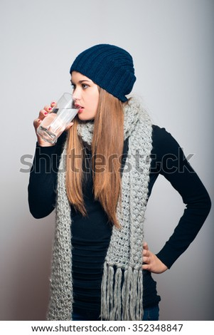 Winter girl drinking a glass of water. Lifestyle studio photo isolated portrait of a woman on a gray background. - stock photo
