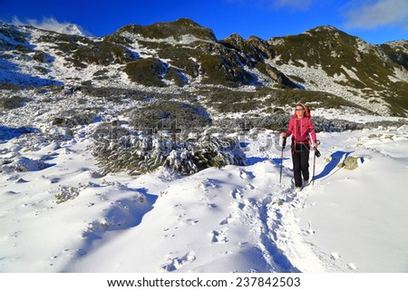 Winter hike with woman walking snow covered trail on the mountain - stock photo