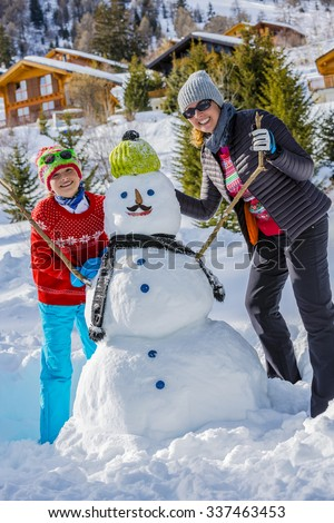 Winter holiday, Christmas, happy family building snowman on ski holiday in mountains - stock photo