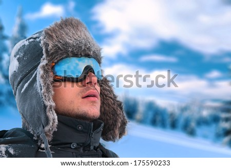 Winter holiday - portrait of a man wearing an ear flap hat and ski glasses with mountains in background  - stock photo