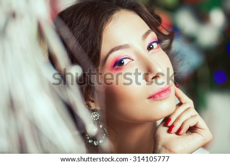 Winter holidays and Girl's best friends concept. Close up portrait of rich young asian woman smiling wearing expensive vintage diamond earrings. Perfect evening make-up. Vintage style. Indoor shot - stock photo