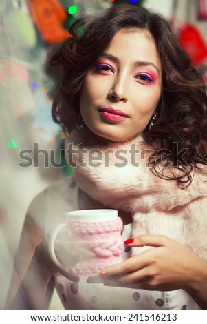 Winter holidays celebration concept. Portrait of doll like brunette in retro polka-dot sleeveless dress drinking tea or coffee in restaurant, cafe. Pink fur scarf on her neck. Close up. Indoor shot - stock photo