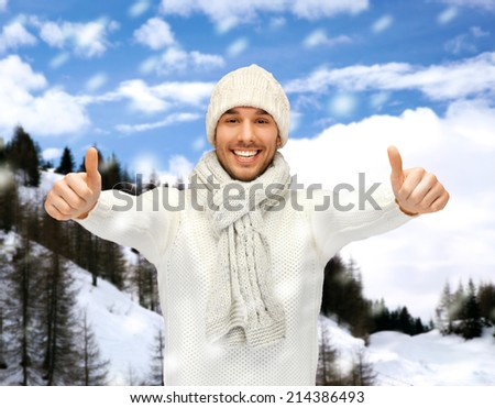 winter holidays, vacation and lifestyle concept - handsome man in warm sweater, hat and scarf showing thumbs up - stock photo
