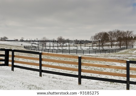 Winter horse farm scene with freshly fixed fence. - stock photo