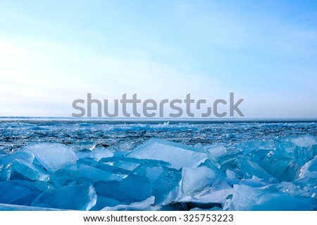 Winter. Ice on the surface of Lake Baikal.  Cracks in the ice surface. Ice storm. Used deep blue toning of the photo. - stock photo