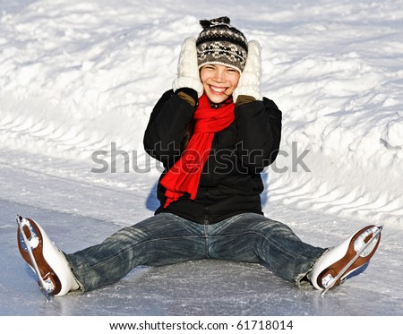 Winter Ice skating Girl having fun on ice skate rink outdoors. Cute photo of young smiling asian woman sitting on the ice. From Quebec City, Canada. - stock photo
