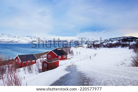 Winter in Norway - mountains with red house and the ocean. - stock photo