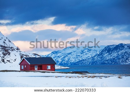 Winter in Norway - mountains with red house near the ocean. - stock photo