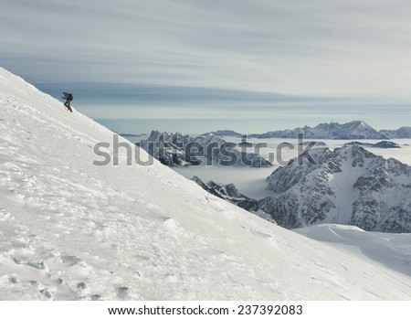 Winter in the mountains; hiker ascending the snowy ridge towards Mt. Stol  (2236 m) in Karavanke Alps. Several filters are applied for vintage effect.  - stock photo