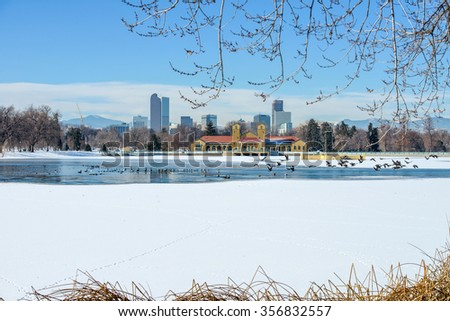 Winter Lake At Downtown Denver - A winter view of frozen lake in a city park, with city skyline and front range mountains in the background, at east-side of Downtown Denver, Colorado, USA. - stock photo