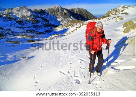 Winter landscape and woman backpacker on snow covered trail, Retezat mountains, Romania - stock photo