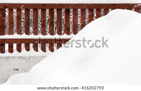 Winter landscape backyard private farmhouse with a red fence and snowbank in foreground - stock photo
