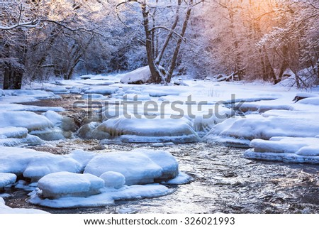 Winter landscape by a river in the sunset - stock photo