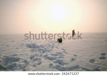 winter landscape fisherman on the river at dawn foggy frosty morning  - stock photo