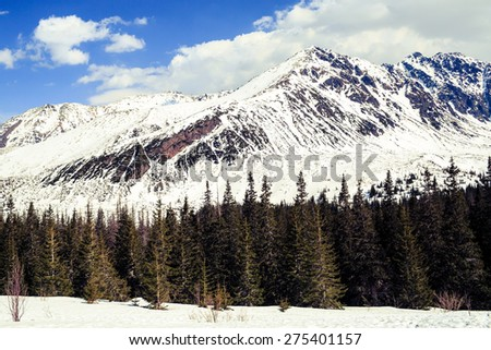 Winter landscape in beautiful Tatra Mountains. White mountain ridge with snow over blue sunny sky in Poland - stock photo