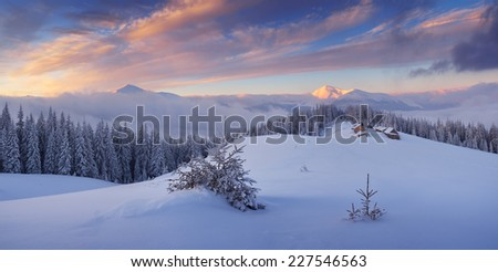 Winter landscape in the mountains. Frosty morning with a beautiful sky. The village of shepherds on a mountain meadow. Carpathians, Ukraine - stock photo