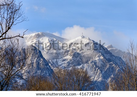 Winter landscape in the mountains. Horizontal alpine landscape in the Transylvanian mountains in Romania, Europe with cross on peak. - stock photo
