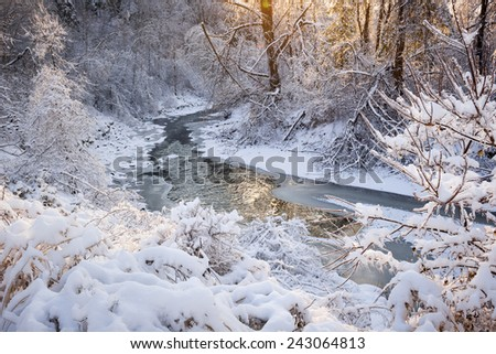 Winter landscape of snow covered forest with flowing river after winter snowstorm glowing and sparkling in warm sunshine. Ontario, Canada. - stock photo