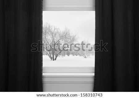 Winter landscape seen through the window with black curtains. - stock photo
