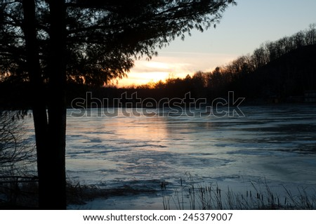 Winter landscape: Sunset over a frozen lake - stock photo