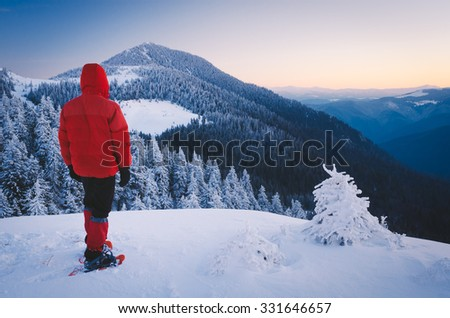 Winter landscape. Tourist in snowshoeing in red jacket standing on the hill. Christmas view. Carpathians, Ukraine, Europe. Low contrast. Color toning - stock photo