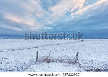winter landscape with a field and white snow at sunrise with a dramatic blue sky in the background - stock photo