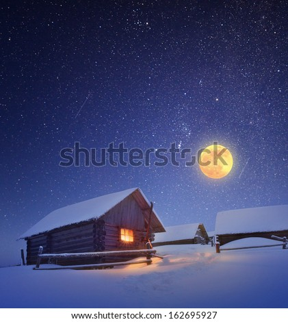 Winter landscape with a starry sky and the full moon. The light in the cabin in the mountains - stock photo