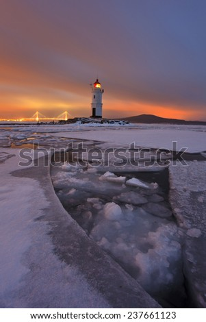 Winter landscape with a view of the lighthouse, iced sea and night city lights - stock photo