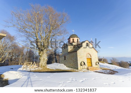 Winter landscape with countryside church on the mountain top - stock photo