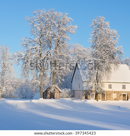 Winter landscape with cozy German style rural cottages in Latvian countryside on a sunny day - stock photo