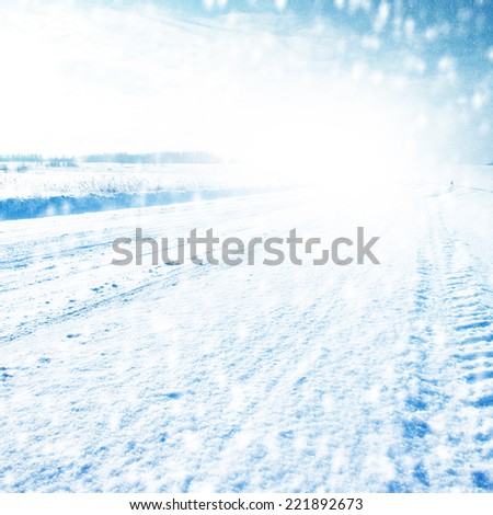 Winter landscape with empty country road, sky and snowfall. - stock photo