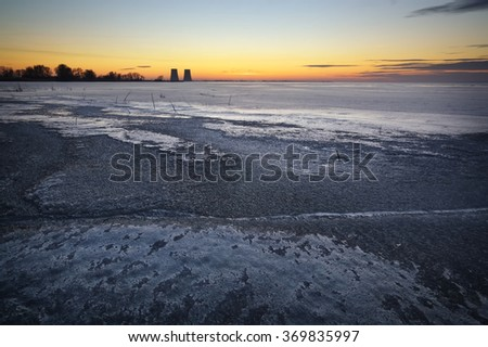 Winter landscape with frozen lake and power plant. - stock photo